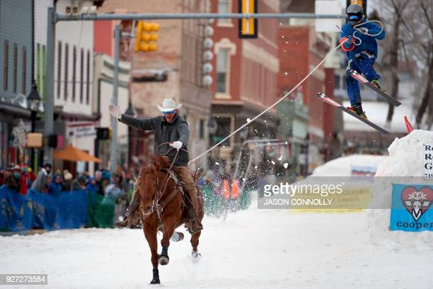 Rider Zach West races down Harrison Avenue while skier Shawn Gerber airs out off the final jump of the Leadville ski joring course during the 70th...