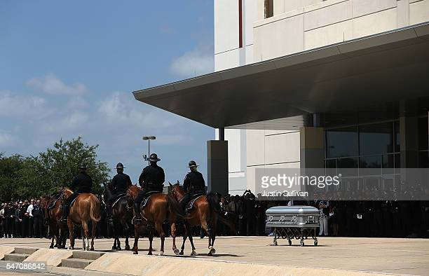 A riderless horse walks past the casket of slain Dallas Area Rapid Transit police officer Brent Thompson after a funeral service at the Potter's...