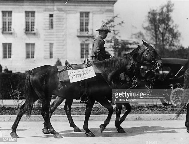 Riderless horse with a sign saying, 'I am willing to got to France are you' ? is being led through the streets of Washington by a member of the...