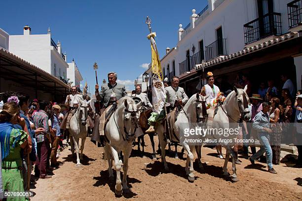 Riders and pilgrims of the Brotherhood of El Rocio from Triana procession through the streets of the village, accompanying his Brotherhood, dressed...