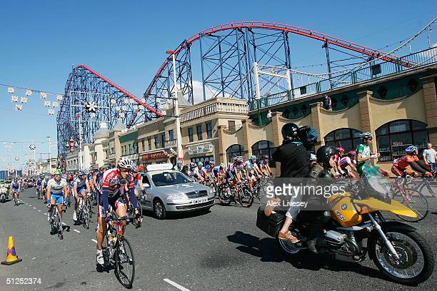 Riders and TV camera motorbikes pass the Pepsi Max Europe's tallest and fastest rollercoaster ride as they cycle down the promenade in Blackpool...