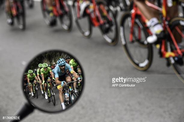 Riders are seen in a wing mirror during the 178 km tenth stage of the 104th edition of the Tour de France cycling race on July 11 2017 between...