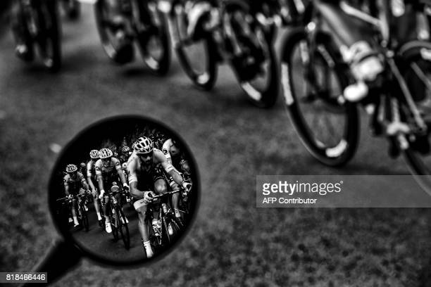 Riders are seen in a wing mirror during the 178 km tenth stage of the 104th edition of the Tour de France cycling race on July 11, 2017 between...