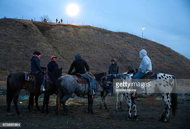 Riders bring their horses to the edge of the water for a drink as police stand atop the hill on Turtle Island in Cannon Ball ND near Standing Rock on...