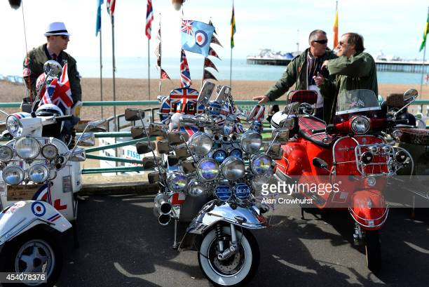 Riders chat about their scooters during the Brighton Mod weekender on August 24 2014 in Brighton England This August Bank holiday will see many Mods...