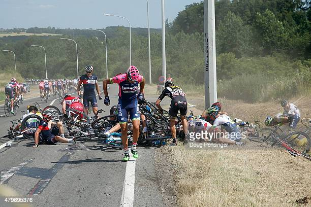 Riders collect themselves after a crash with 65km left to race in stage three of the 2015 Tour de France from Anvers to Huy on July 6 2015 in Huy...