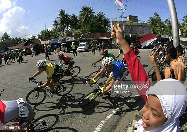 Riders compete during stage six of the 2013 Tour de Singkarak a 1445 KM road stage from Pariaman to Painan on June 6 2013 in Padang Indonesia