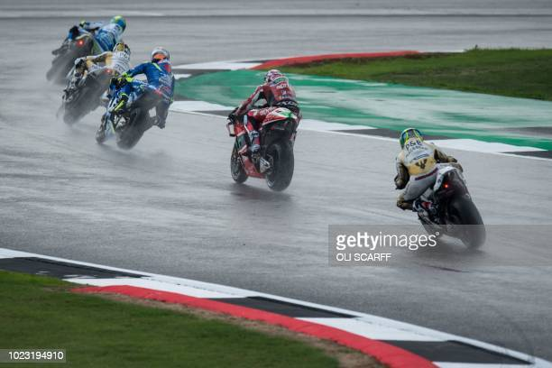 Riders compete in wet weather during a MotoGP qualifying session of the motorcycling British Grand Prix at Silverstone circuit in Northamptonshire...
