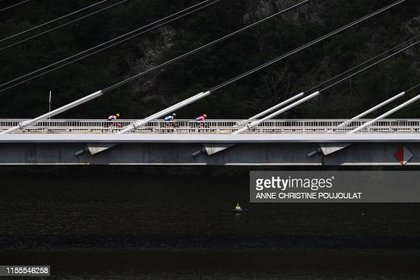 Riders cross a bridge during the ninth stage of the 106th edition of the Tour de France cycling race between Saint-Etienne and Brioude, on July 14,...