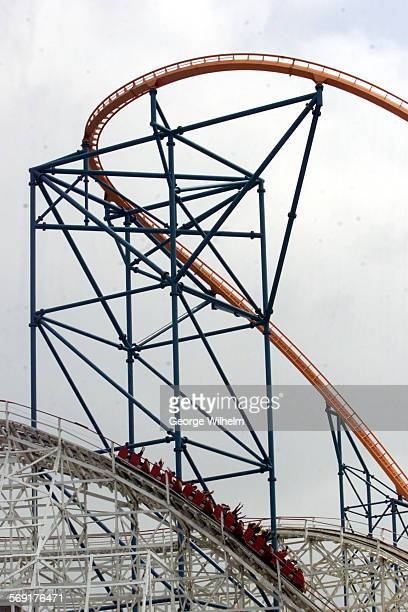 Riders enjoy the Colossus wooden roller coaster Saturday in the shadow of Goliath after the ride was shut down following the death of a 28–yuear–old...