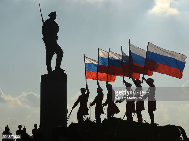 Riders hold the Russian national flag next to a bronze statue of a Russian soldier in Moscow on August 22 during celebrations of the National Flag...