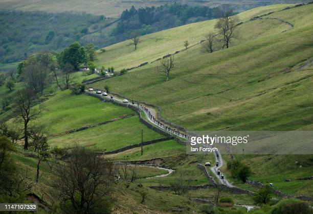 Riders in the peloton approach the bottom of the Cote de Park Rash ascent near the village of Kettlewell in the Yorkshire Dales during the fourth and...