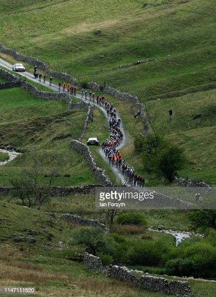 Riders in the peloton approach the Cote de Park Rash ascent near the village of Kettlewell in the Yorkshire Dales during the fourth and final stage...