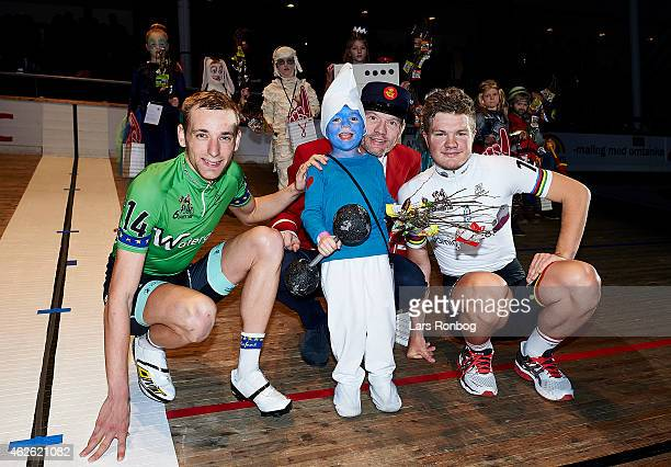 Riders Jesper Morkov and Mathias Krigbaum of Denmark and Jorgen HK Jepsen of Post Danmark poses with a kid winning the best costume contest in the...
