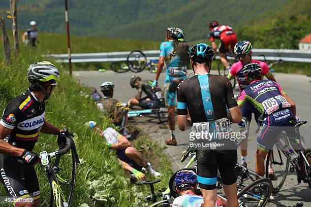 Riders lie on the roadside after a crash during the eleventh stage of the 2014 Giro d'Italia a 249km medium mountain stage between Collecchio and...