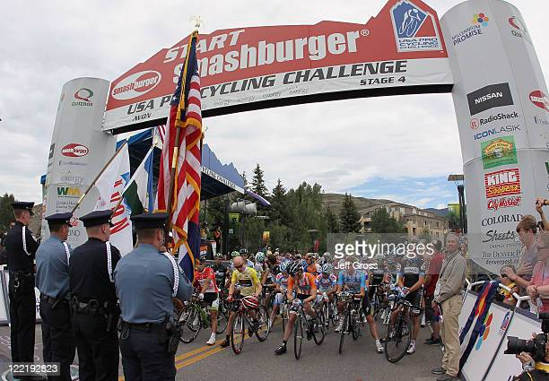 Riders observe the National Anthem during the start of stage four of the 2011 USA Pro Cycling Challenge from Avon to Steamboat Springs on August 26...