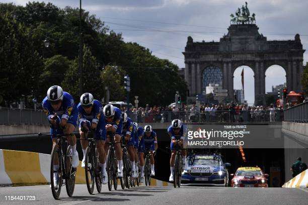 Riders of Belgium's Deceuninck-Quick-Step cycling team compete with the triple arches of the Arcades du Cinquantenaire in background in the second...