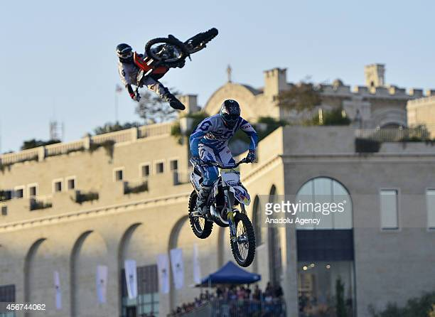 Riders of FMX4Ever perform motorcycle stunts during the 2014 edition of the Formula 1 Peace Road Show on October 6 2014 in Jerusalem Israel The...