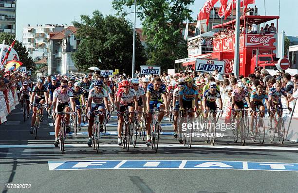 Riders of the Tour de France cross the finish line together at the end of the 16th stage between Tarbes and Pau on July 19 in memory of Italian rider...
