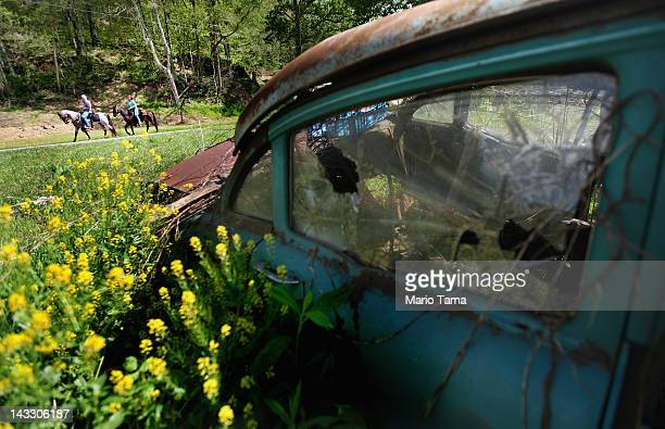 Riders pass an abandoned car during the Owsley County Saddle Club trail ride on April 20 2012 in Booneville Kentucky The trail ride attracts riders...