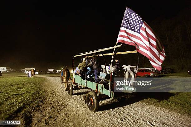 Riders pass in a wagon with an American flag at the Owsley County Saddle Club trail ride on April 19 2012 in Booneville Kentucky The trail ride...
