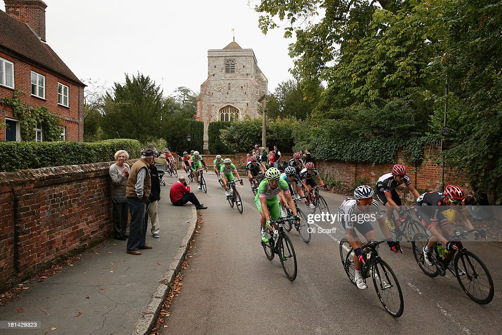 Riders pass through the small village of Puttenham during stage seven of the Tour of Britain from Epsom Racecourse to Guildford on September 21, 2013 in Puttenham, England. Today's 155km stage is the penultimate one before the race concludes in central London tomorrow. Sir Bradley Wiggins, riding for Team Sky Procycling, currently leads the race beginning today's stage with a 32 second advantage.