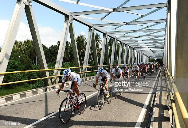 Riders pass trough bridge in Lubuk Buaya area during the Stage 6 Tour de Singkarak 2013, start from Gandoriah Beach Pariaman to Painan, distance...