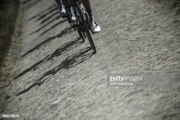 Riders pedal through a cobblestone section during the ninth stage of the 105th edition of the Tour de France cycling race between Arras and Roubaix,...