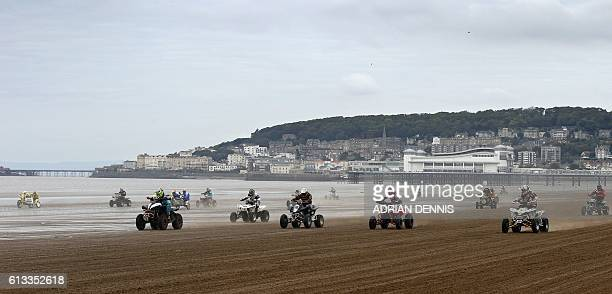 Riders race down the beach during the Adult Quad and Sidecar race during the 2016 HydroGarden Weston Beach Race in WestonsuperMare south west England...