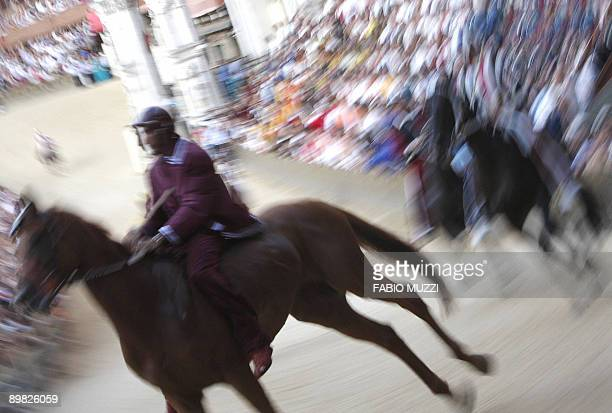 """Riders round the curve of Casato as thousands of people attend in the main square at the """"Il Campo"""", the Palio horse race in Siena on August 16,..."""
