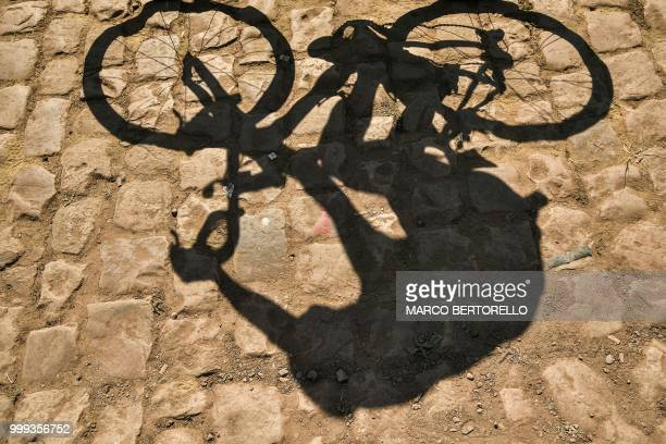 A rider's shadow is cast on cobblestones prior to the start of the ninth stage of the 105th edition of the Tour de France cycling race between Arras...