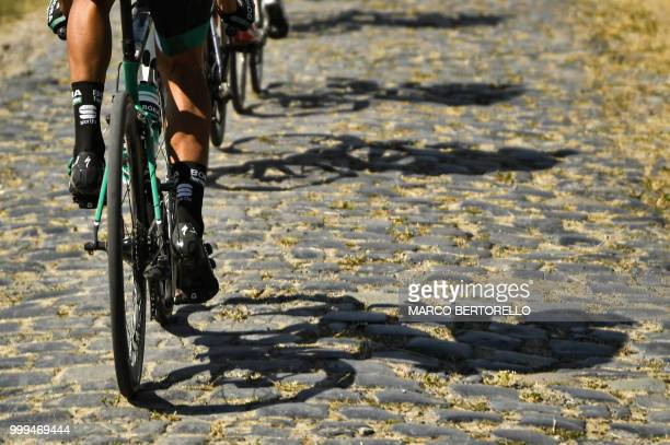 Riders' shadows are cast on cobblestones during the ninth stage of the 105th edition of the Tour de France cycling race between Arras and Roubaix,...