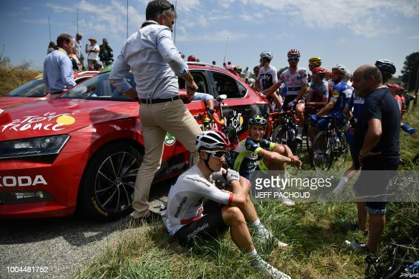 Riders sit after General Director of the Tour de France France's Christian Prudhomme halted the race following a farmers' protest who attempted to...
