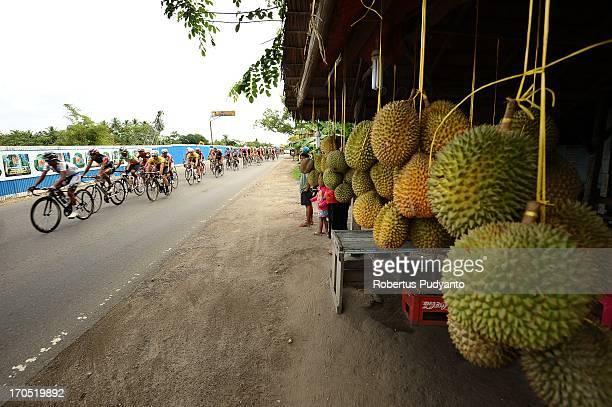 Riders speeding their bike pass through durians seller during Stage 7 Tour de Singkarak 2013 in Padang.
