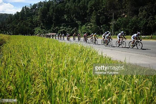 Riders speeding their bike through the rice field in stage 5 Tour de Singkarak 2013 start from Sawahlunto to Muara Labuh. Mileage of 138.5 km with an...