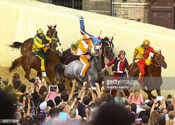 Riders take part in the famous Palio Di Siena horse race that is held twice each year on July 2 and August 16 at Siena's Piazza del Campo square in...