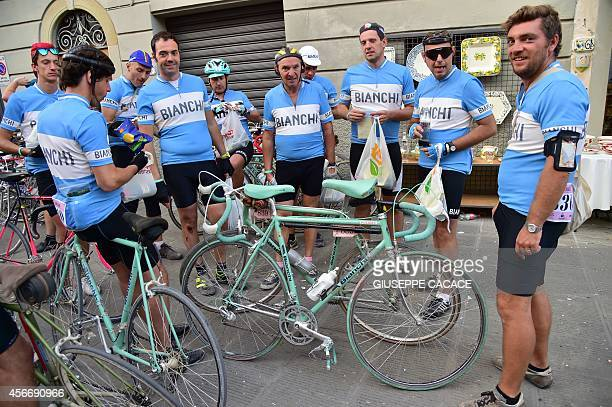 Riders wearing jerseys of the Italian brand 'Bianchi' pose during L'Eroica a retro cycling event on October 5 2014 in Gaiole in Chianti near Siena...