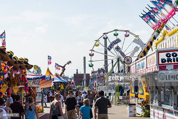 rides, games and crowds of people at minnesota state fair - midway stock photos and pictures