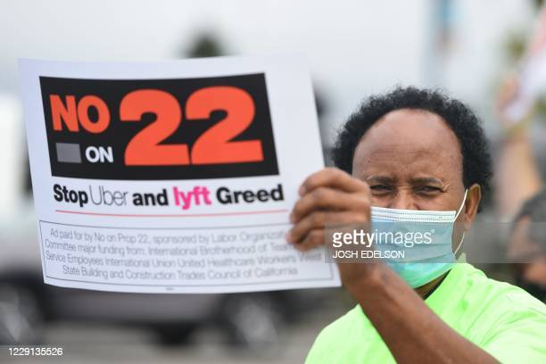 Rideshare driver holds up a sign supporting a no vote on Prop 22 in Oakland, California on October 9, 2020. - Ahead of a referendum that could upend...