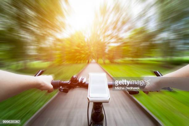 Riding a bike first person perspective. Smartphone on handlebar. Speed motion blur