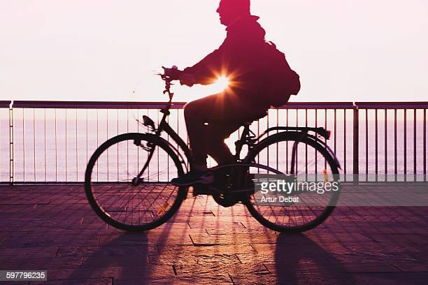 Riding a bike in Barcelona boardwalk on sunrise.