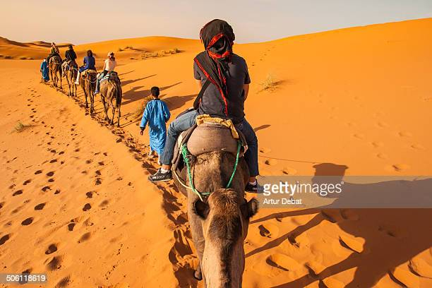 Riding a camel in first person view with a group of people in row in the dunes desert of Erg Chebbi in the country of Morocco. Africa.