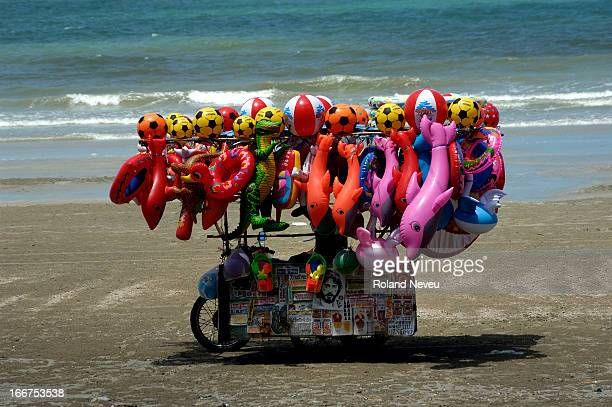 Riding a makeshift motorcycle loaded with balloons and colorful children buoy a man cruise along the beach looking for buyers