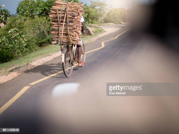 POV riding a motorbike along the road near Trincomalee aka Gokanna overtaking a bicycle with a big load of wood