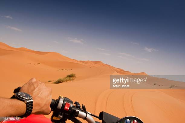 Riding a quad in the desert dunes.