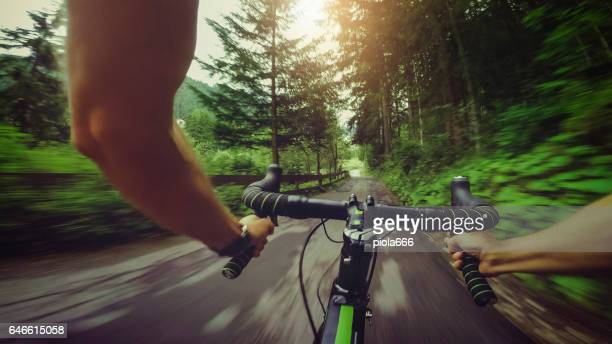 pov riding a road racing bicycle in the forest - handlebar stock photos and pictures