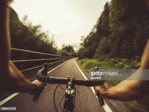 POV riding a road racing bicycle in the forest