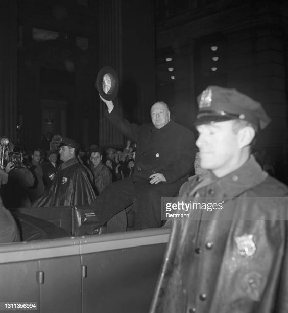 Riding an open car in the rain, Winston Churchill, Britain's wartime Prime Minister, rides along lower Broadway waving his hat to the crowd that...