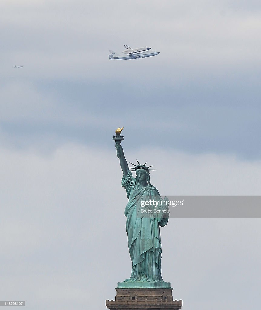 Riding atop a 747 shuttle carrier aircraft, the space shuttle Enterprise flies past the Statue of Liberty in New York Harbor on April 27, 2012 in New York City. Enterprise, which was flown from Washington, DC, will eventually be put on permanent display at the Intrepid Sea, Air and Space Museum.