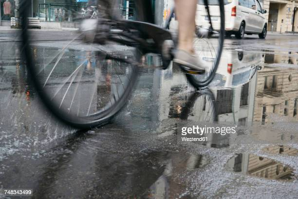 Riding bicycle in the city on a rainy day, partial view